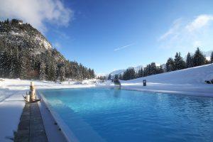 Beheizter Außenpool in veschneiter Landschaft im Hotel Schlossanger Alp in Pfronten im Allgäu