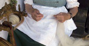 Alte Handwerkskunst: Frau am Spinnrad