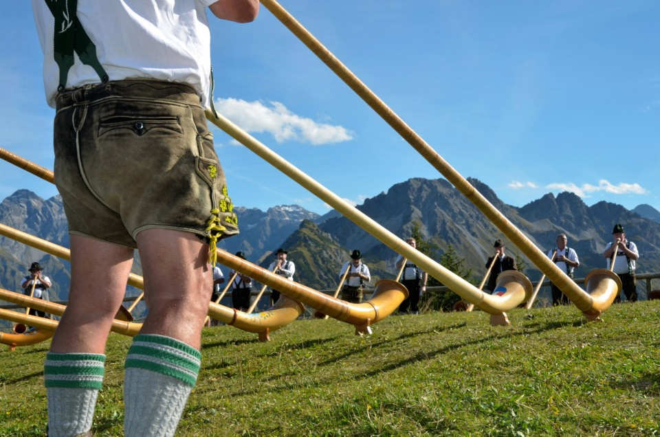 Alphornspieler mit Tracht im Gebirge