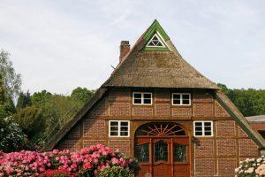 Reetgedecktes Haus im Ammerland mit Rhododendron-Blüten