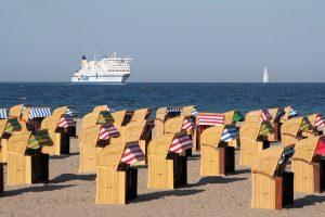 Strandkörbe an der Ostsee bei Travmünde mit Fährschiff im Hintergrund