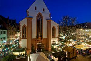 Freiburger Kirche mit Weihnachtsmarkt