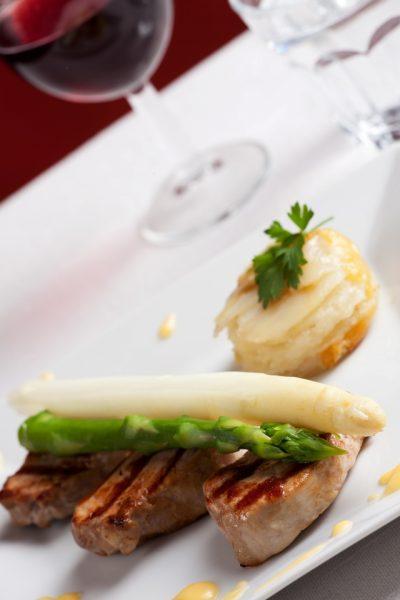 Nahaufnahme von Kartoffelgratin und weißem und grünem Spargel auf einer Scheibe Filet, Emma Metzler