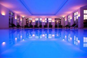 abendlich beleuchter Pool im Badehaus im Parkhotel Surenburg