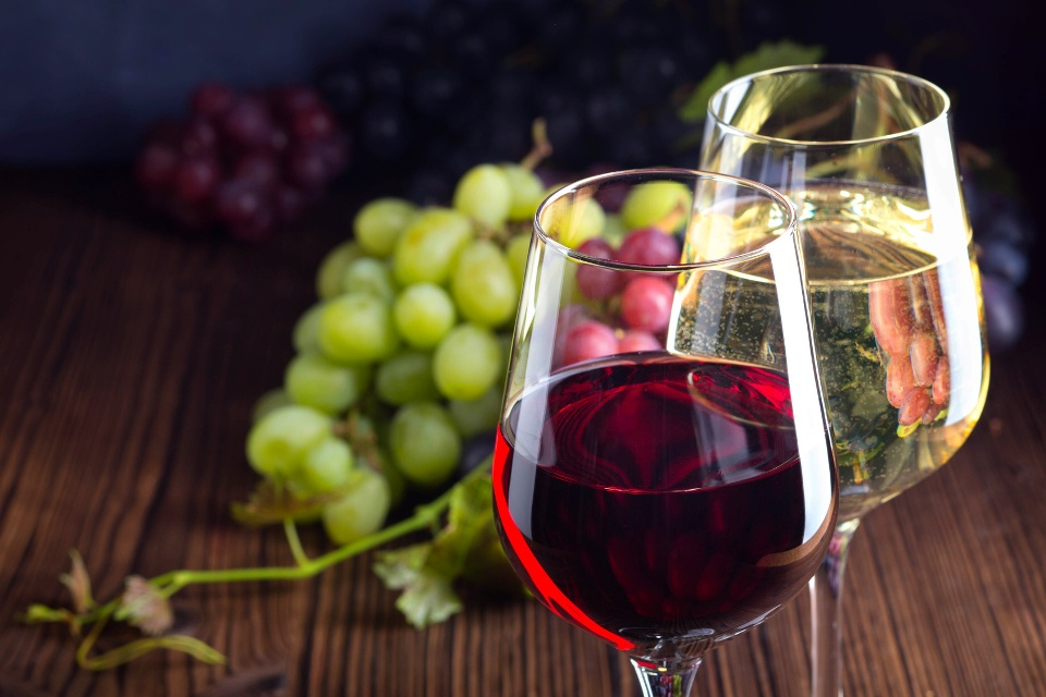 Gläser mit Rot- und Weißwein mit Trauben