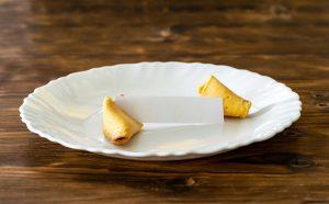 Glückskeks liegt auf einem weißen Teller auf dunklen hintergrund mit einem leeren Zettel