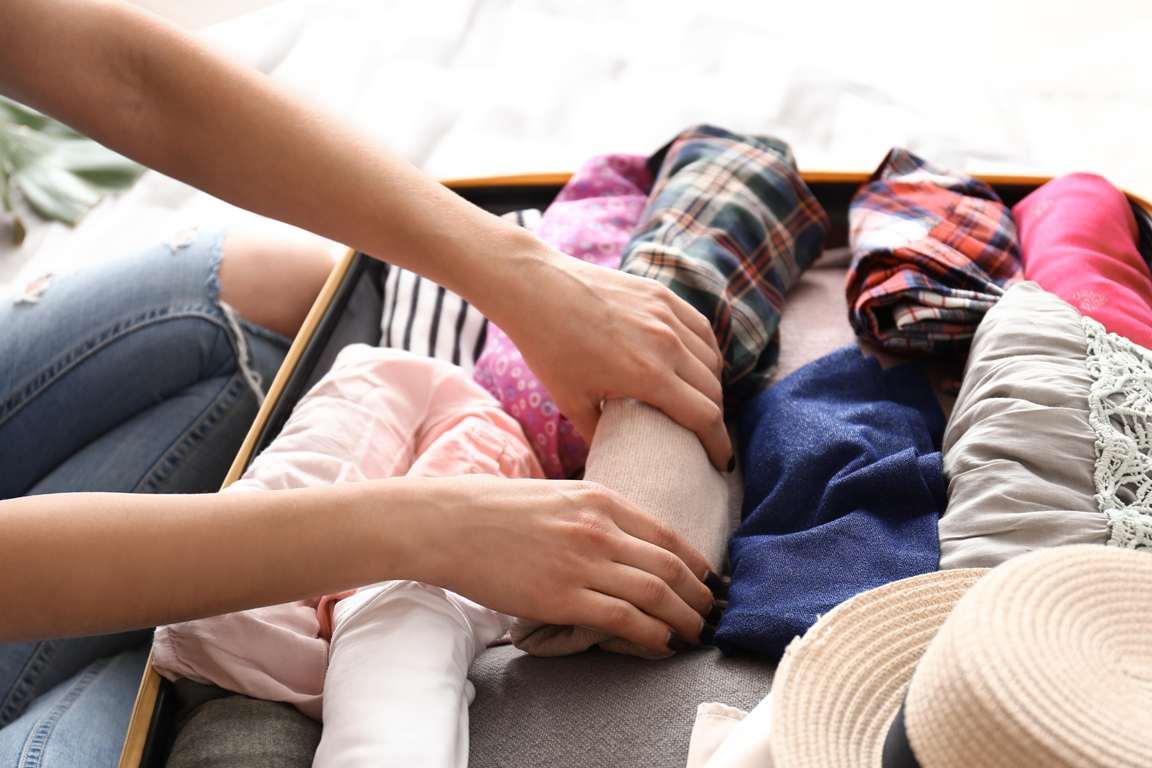 eingerollte Kleidungsstücke beim platzsparenden Kofferpacken