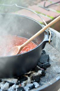 Tomaten andünsten Im gusseisernen Topf auf Holzkohlenfeuer