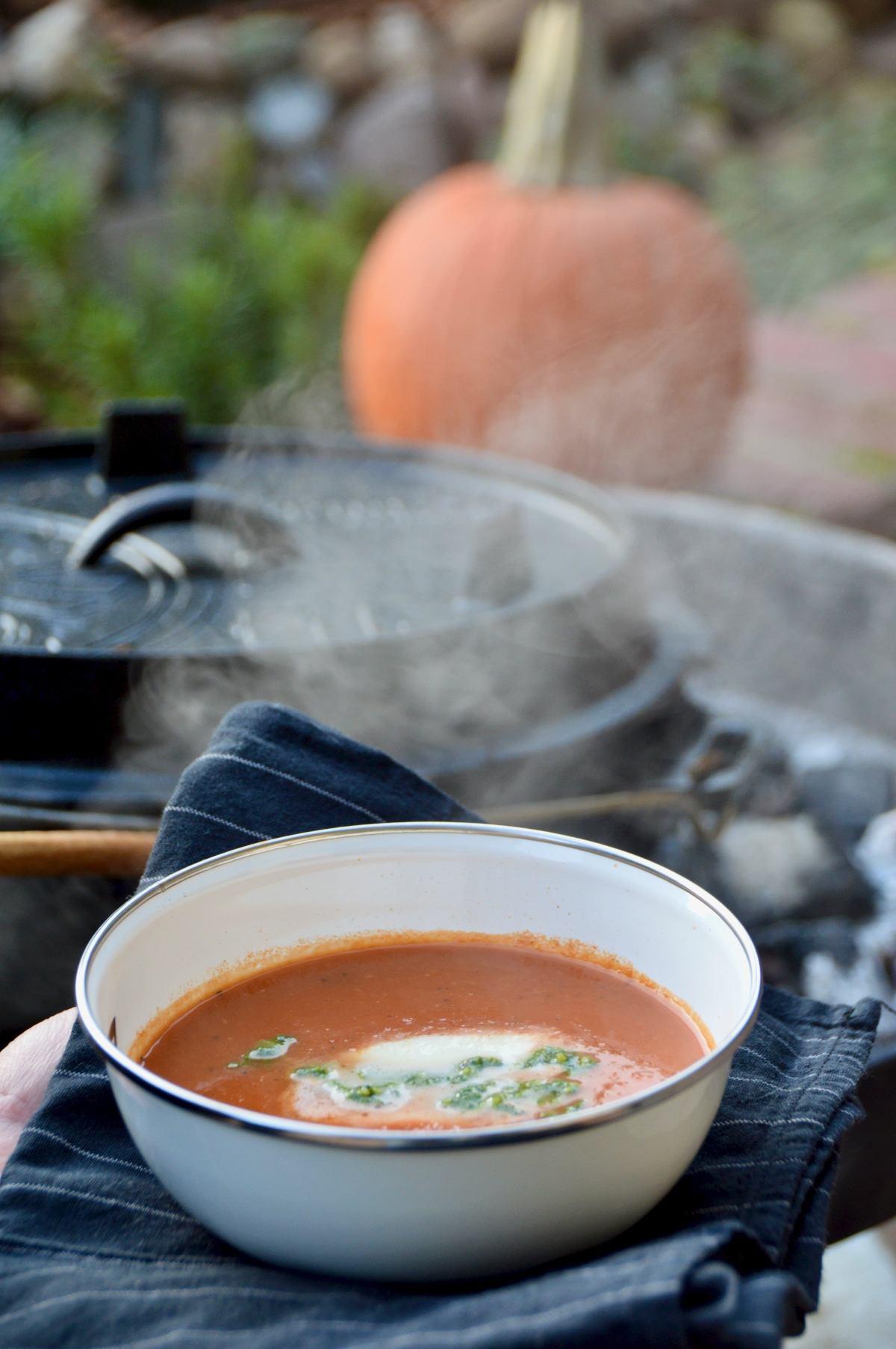 Tomatensuppe auf Holzkohle zubereitet im Freien genießen