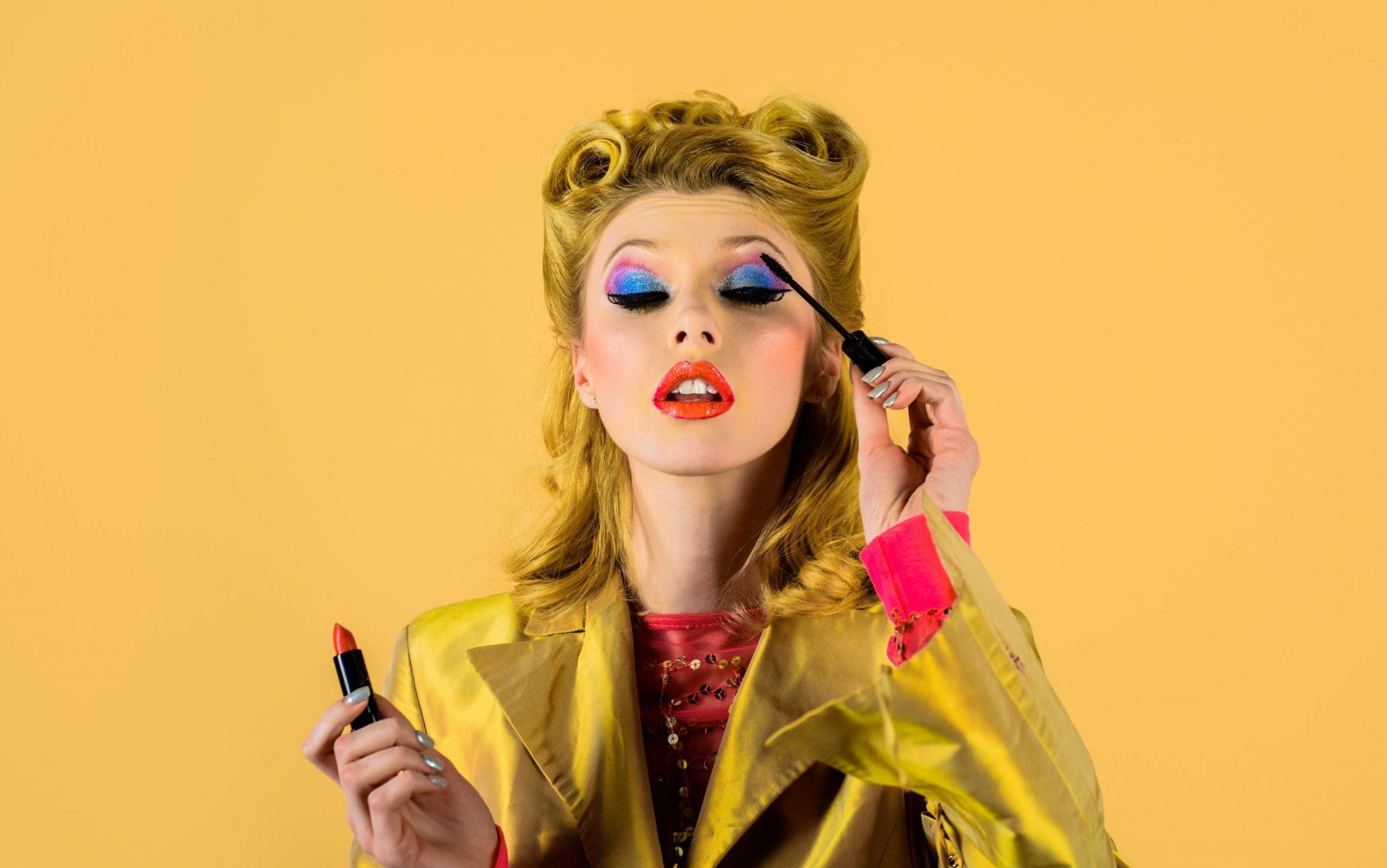 Junge Frau schminkt sich im 50er Jahre Stil