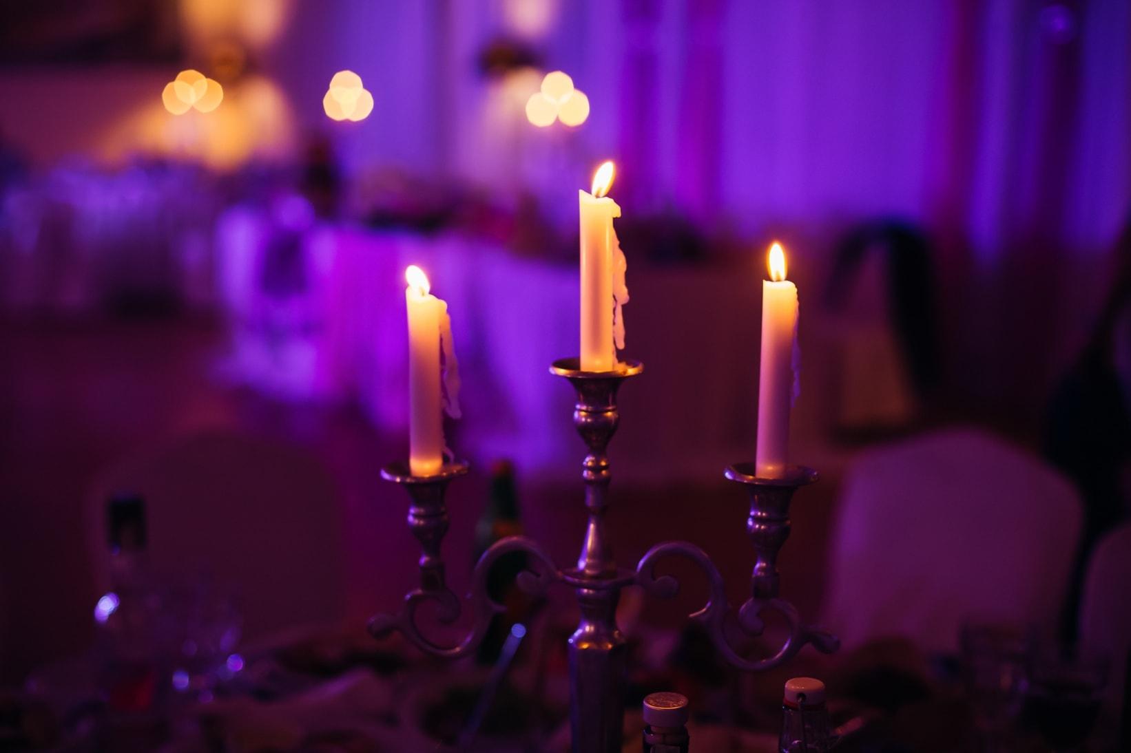Kerzenleuchter in lila beleutschteten Raum