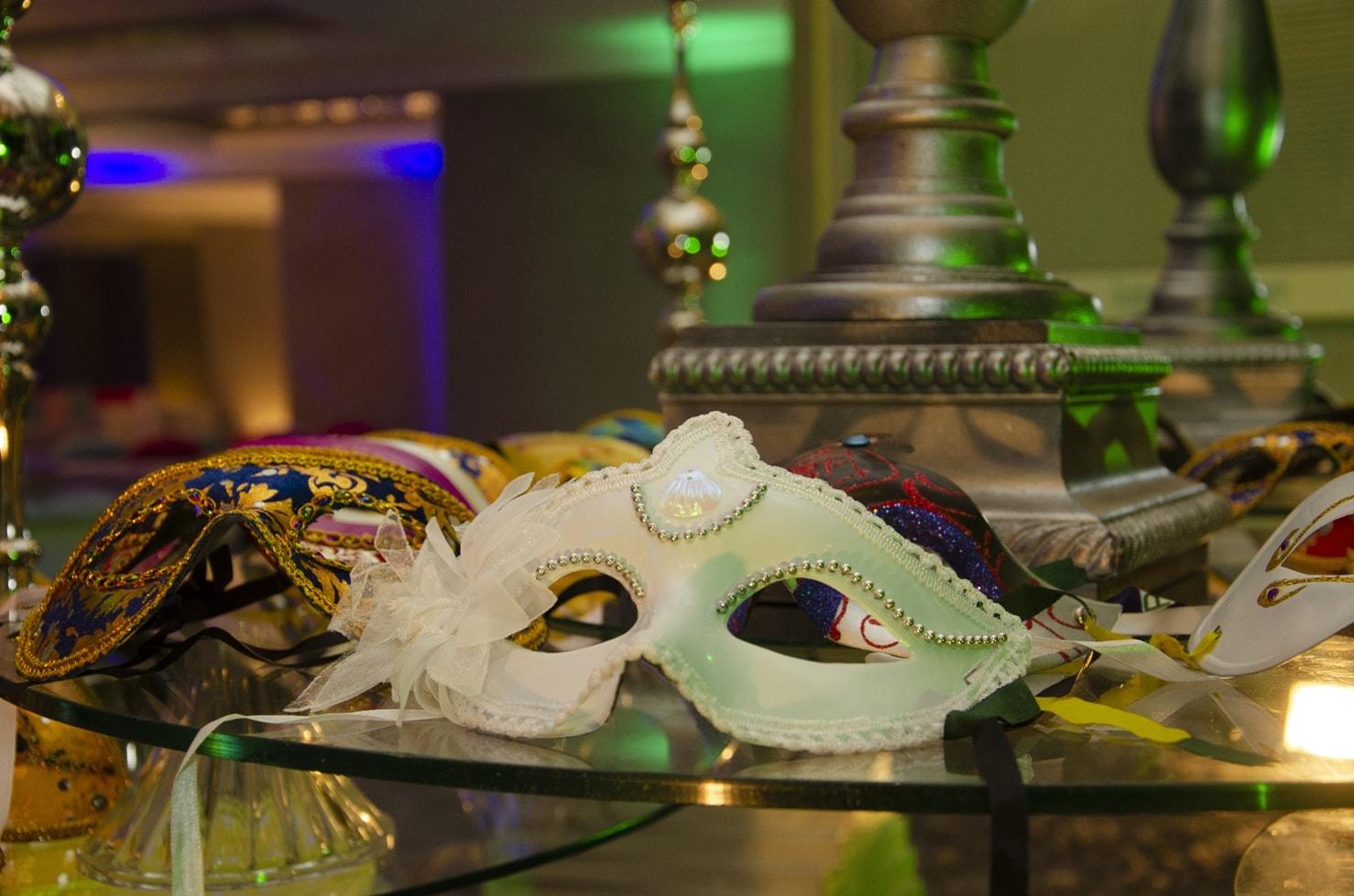 Masken beim Maskenball auf einem Glastisch