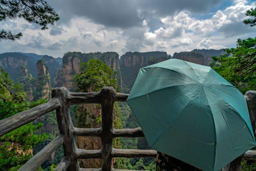 Tourist mit Regenschirm an einem Aussichtspunkt in den Zhangjiajie Bergen in China
