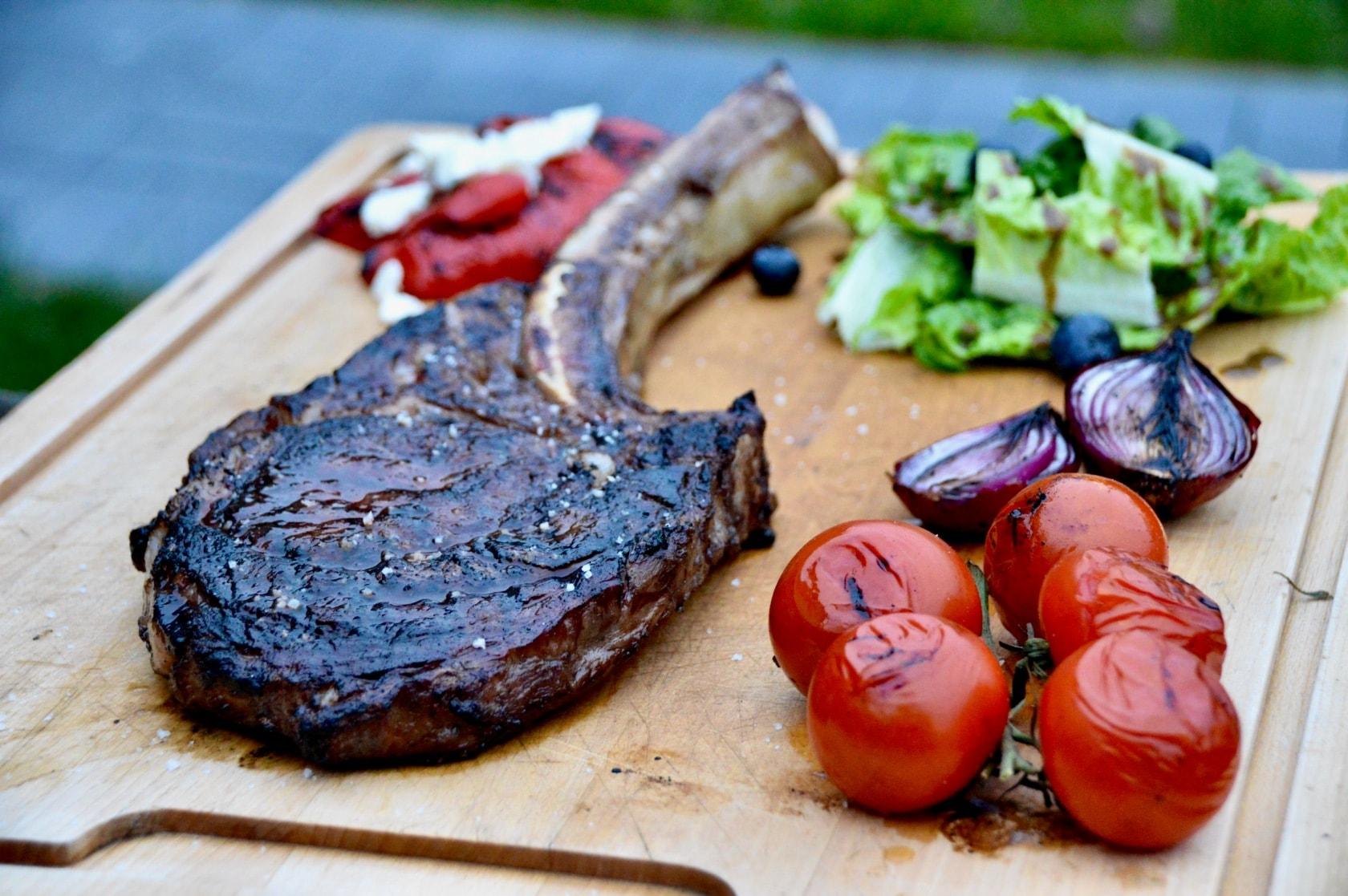 Wagyu Tomahawk Steak gegrillt mit Tomaten und Salat