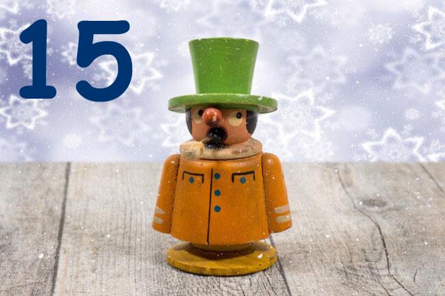 Orangenes Räuchermännchen mit grünem Hut auf Holztisch vor Schneeflockentapete