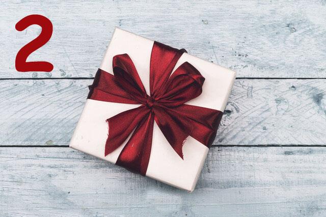 eingepacktes Geschenkschachtel mit dunkelroter Schleife auf weißen Holzdielen