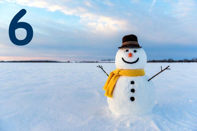 Schneemann auf Schneebedeckem Feld vor Sonnenuntergang