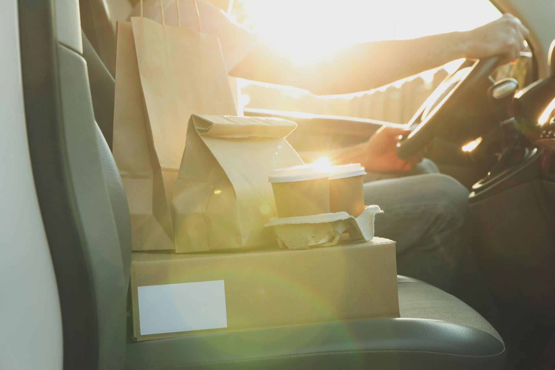 Lieferservice Essen in braunen Päckchen auf Beifahrerseitz