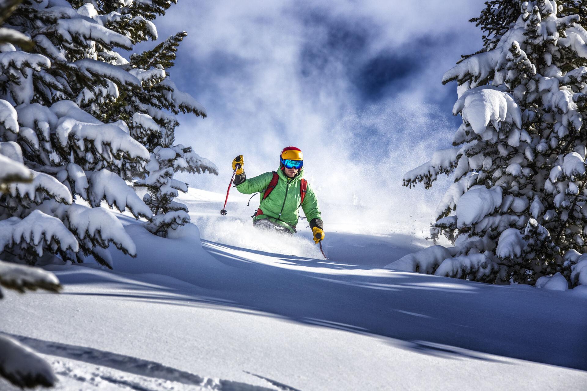 Skifahren: Skifahrer fährt durch tiefen Neuschnee