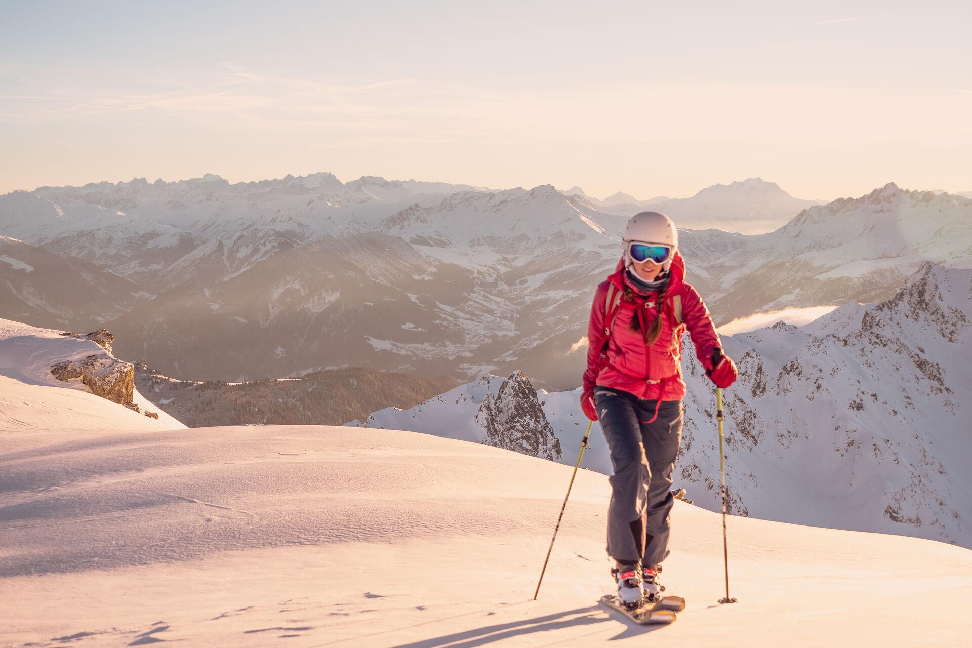 Skifahren: Junge Frau auf Skiwandertour mit Gipfelpanorama