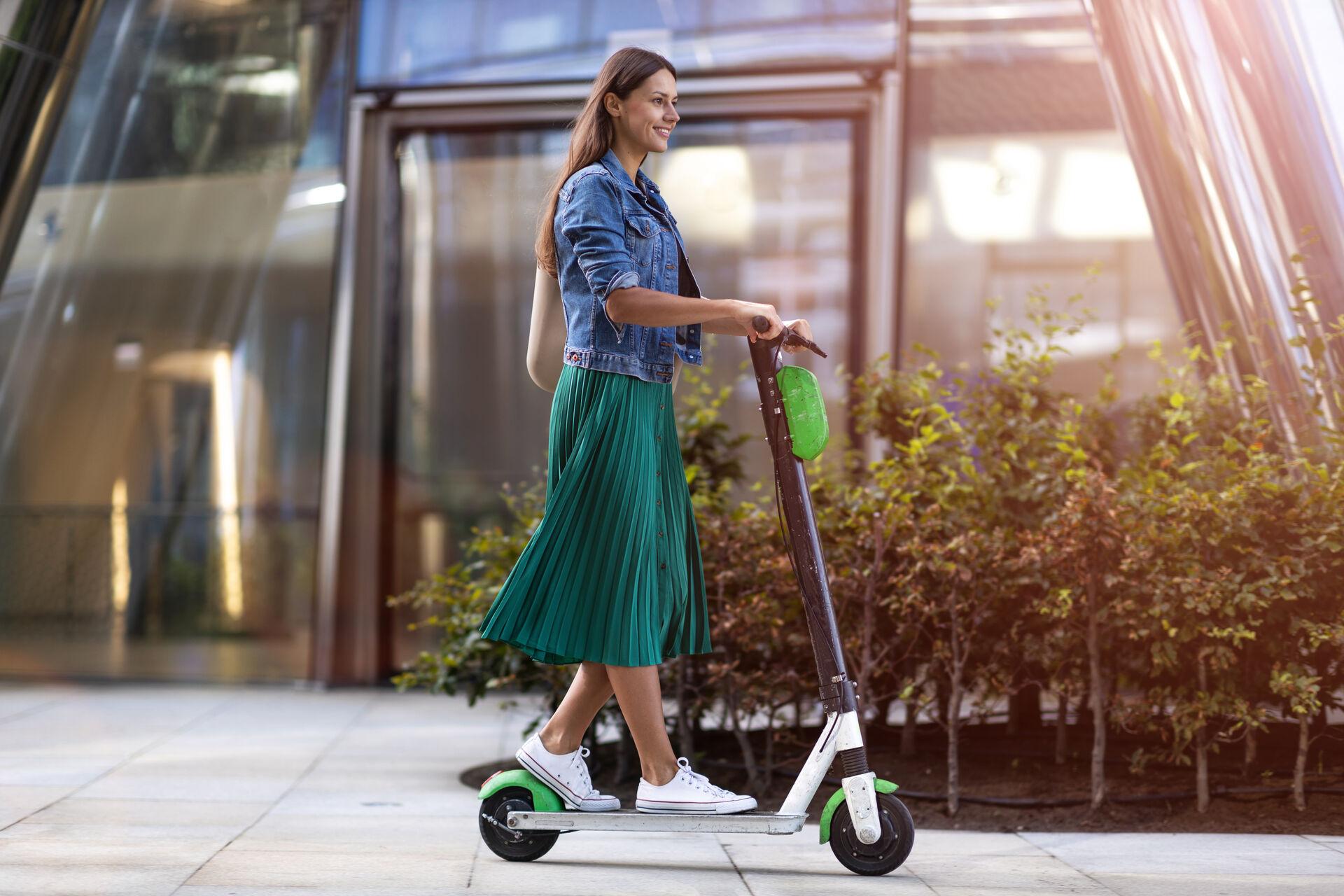 Frau fährt mit dem Scooter durch die Stadt
