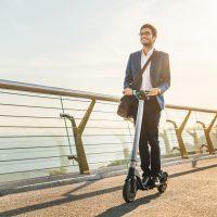 Mann fährt mit dem Scooter über die Brücke