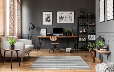 wohnliche Home Office im Wohnzimmer vor grauer Wand mit Bildern