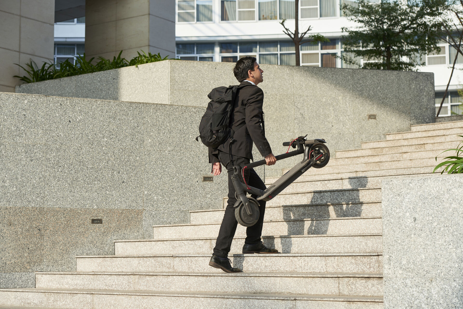Mann läuft treppauf mit zusammengeklapptem Scooter