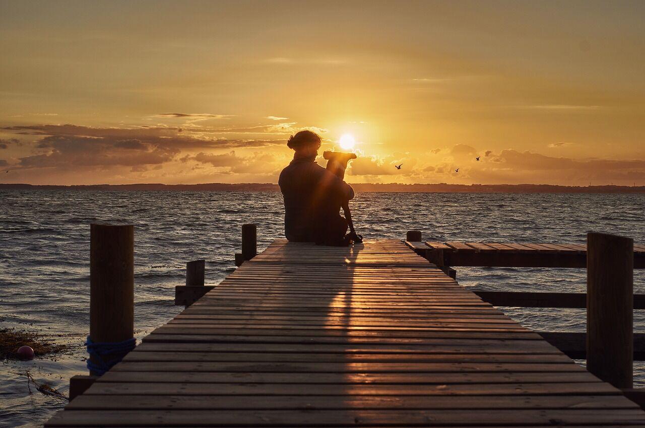 Frau mit Hund auf Steg im Sonnenuntergang