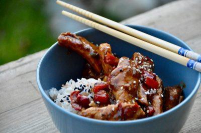 Sichuan-Chicken mit Reis in einer Schale mit Stäbchen